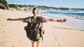 Blonde woman walking on sandy beach near the ocean