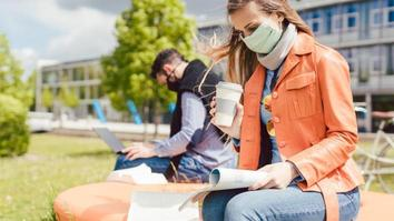 Woman student on university campus learning wearing face mask